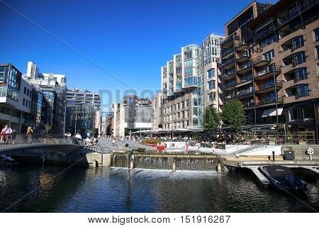 OSLO NORWAY - AUGUST 17 2016: People walking on wonderful modern residential district Aker Brygge with lux apartments shopping culture and restaurants in Oslo Norway on August 172016.