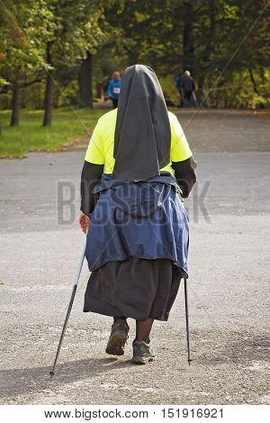 Catholic Nun in park - Nordic walking