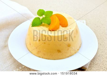 Dessert panna cotta cheesecake with apricots in a white plate on a napkin on the background of a granite table