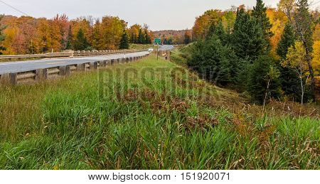Fall Road Trip. Highway 28 in Michigan's Upper Peninsula crosses the Sturgeon River and winds through the northern forest with autumn foliage.