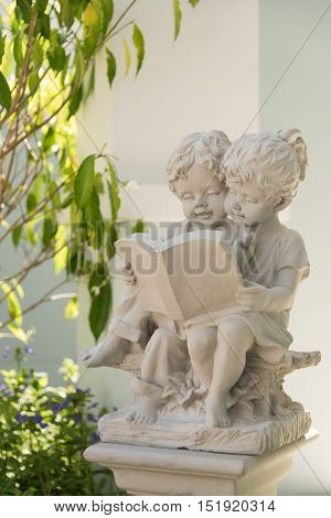 Children statue are reading book together in a garden.