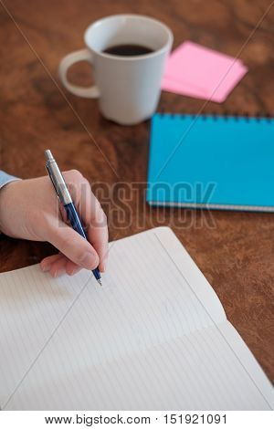 Hand Writing On A Copy Book On Wooden Table
