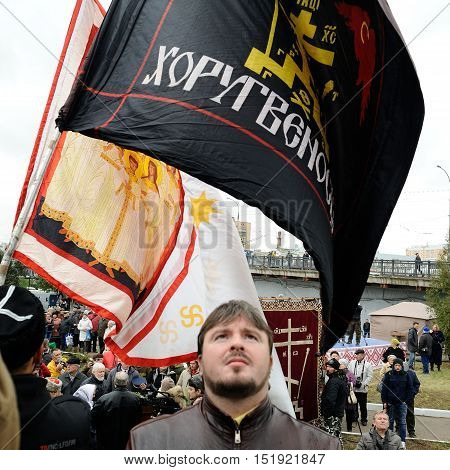 Orel Russia - October 14 2016: Ivan the Terrible monument opening ceremony. Man watching black banner of Union of Orthodox Banner-Bearers Russian ultra-orthodox clerical group square
