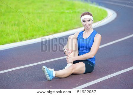Portrait of Caucasian Female Athlete During Body Stretching Exercises Outdoors. Horizontal Shot