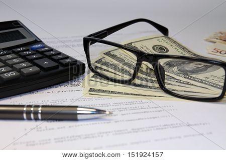 Glasses, Calculator, Bancnote And Pen On Desk