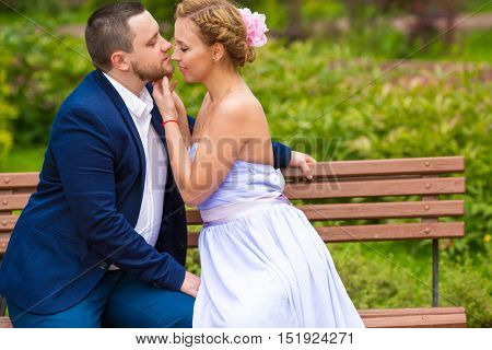 Man and woman embracing and kissing on bench in green summer park