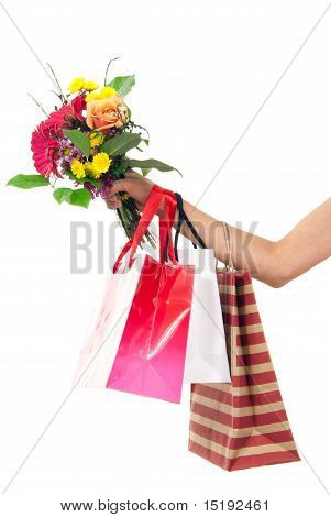 Hand Holding Colorful Shopping Bags And Flowers