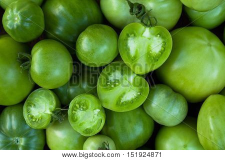 Green Tomatoes. Background Of Green Tomatoes With Green Tomatoes Cut In Half Top View. Bright Green Color.