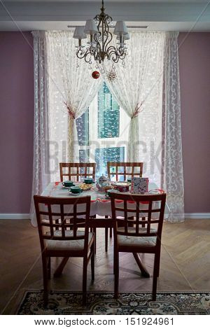 Table served for tea party in room with pink walls, focus on curtain.