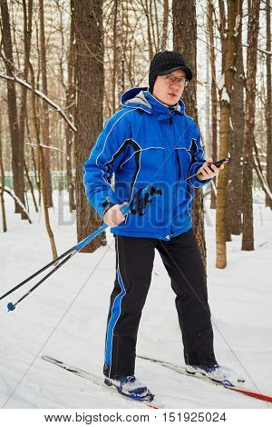 Young man on ski with ski-poles in one hand and cell phone in another in winter snowy park.