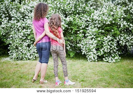 Mother and daughter stand embracing and looking at blooming jasmine bush in park.