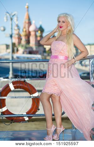 Blonde smiling woman stands on ship deck during sailing in Moscow