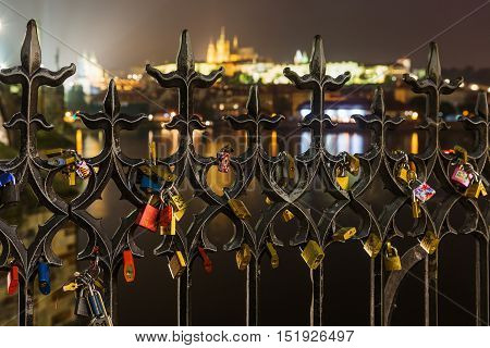 Many Love locks on the fence heart padlock on the Charles Bridge in Prague's Hradcany blurred background. Love locks hang from a bridge in Prague representing secure friendship and romance