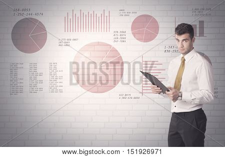 Young sales business male in elegant suit standing in front of brick wall background with lines and pie charts concept
