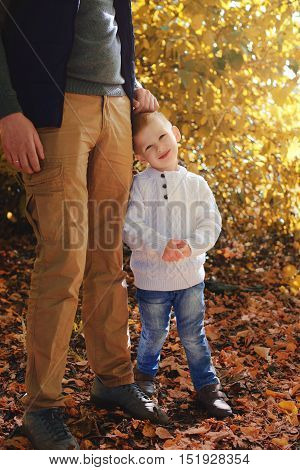 Little boy hugging the leg his father in a park