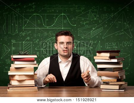 A young passionate male teacher sitting at school desk, reading a book, with area algorythm calculations and numbers on the blackboard concept.