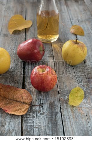 Apple cider in bottle and fresh apples on nature background
