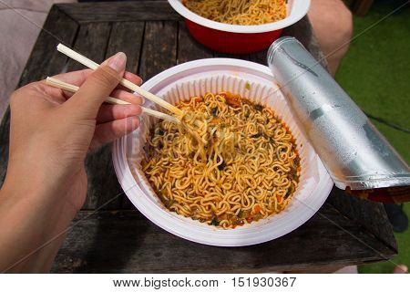 Instant noodle and woman's hand with food sticks