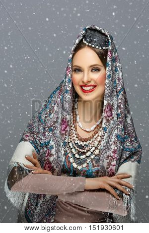 Beautiful young woman with make-up in traditional Russian clothes. Pearl accessories, hat and shawl. Happy expression. Over grey background. Copy space.