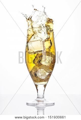 Glass of beer cider with ice cube splash on white background