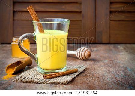 Turmeric golden milk latte with cinnamon sticks and honey. Detox liver fat burner immune boosting anti inflammatory healthy cozy drink. Copy space