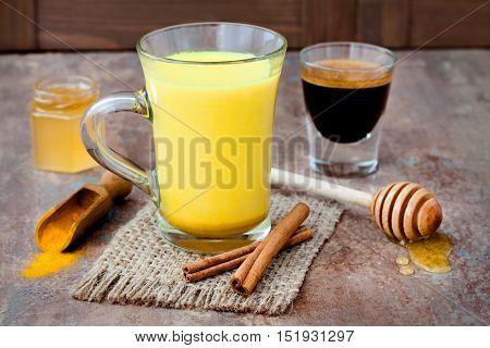 Turmeric golden milk latte with cinnamon sticks and honey. Detox liver fat burner immune boosting anti inflammatory healthy cozy drink