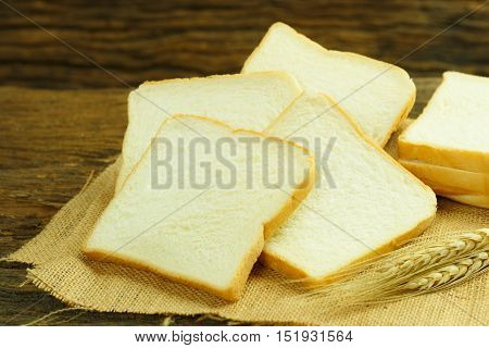 Bread slice. Bread white. Bread on wood. Bread on table. Bread for background. Bread for breakfast. Bread is bakery. Bread is bake. Bread for eat. Bread from wheat. Bread for morning. Bread from flour