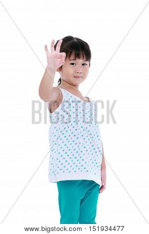 Happy asian child posing at studio isolated on white background. Playful girl showing ok sign. Pretty child looking at camera. Studio shot.