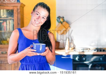 Young woman portrait holding coffee cup with blurred house kitchen background - Beautiful girl with candid smile looking at camera standing inside house living room - Concept of modern healthy female