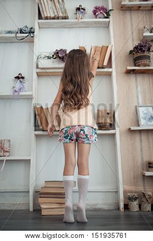 small kid searching interesting book with fairy tale near bookcase;