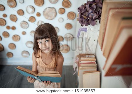 Little Girl Smiling And Reading Book;