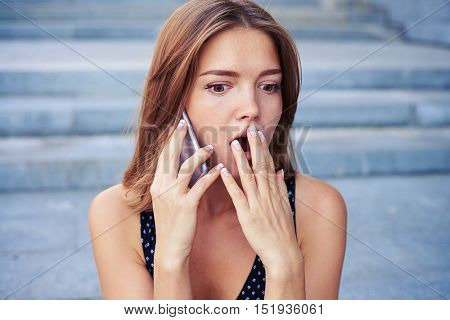 Pretty woman with brown hair looks astonished while speaking on the mobile phone over urban background