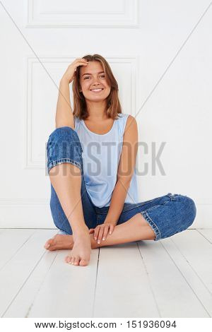 Close-up of young joyous woman in casual outfit sitting on the floor isolated against white background