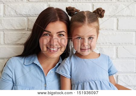 Close-up portrait of tight-knit family of mother and her cute daughter smiling and posing against white background