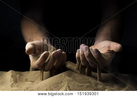 pours sand from his hands on a black background