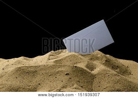 card in the sand on a black background
