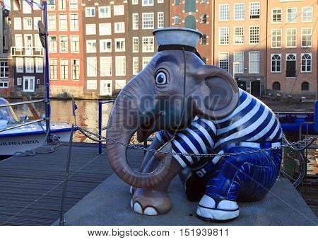 AMSTERDAM, THE NETHERLANDS - MAY 03, 2016: Sculpture of elephant sailor at pier of canal on Damrak street in city center, Amsterdam, Netherlands. Selective focus