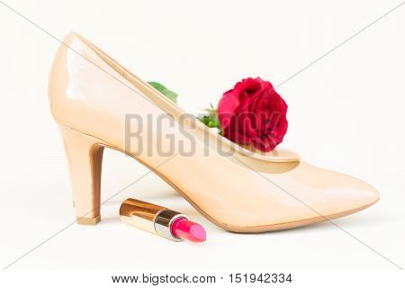 Nude colored high heels still life with red rose flower bud and lipstick