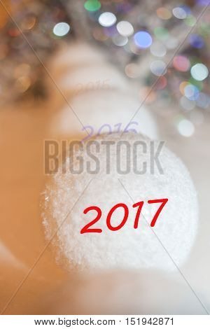 Receding into the distance row of decorative snowballs and lettering 2017 on the front snowball. New Year composition with beautiful bokeh.