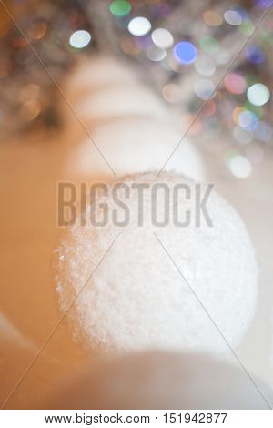 Receding into the distance row of decorative snowballs and beautiful bokeh. New Year composition.