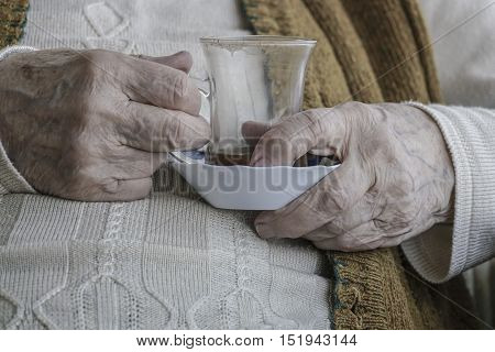 wrinkled hand of a senior woman holding a tea / coffee glass