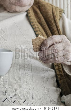 wrinkled hand of a senior woman holding coffee mug and biscuits