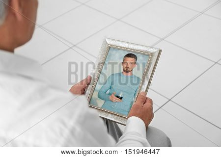 Male hands holding photo frame with picture of man. Happy memories concept.