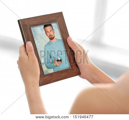 Female hands holding photo frame with picture of man. Happy memories concept.