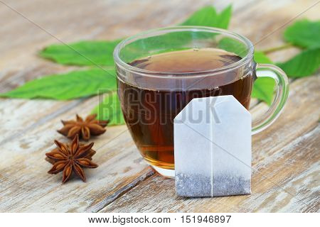 Tea bag leaning against cup of tea and anise