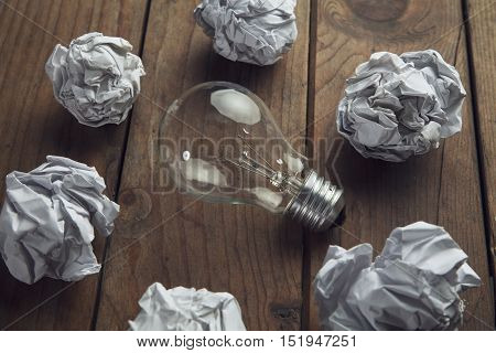 crumpled paper balls arround light bulb brainstorming in the office concept