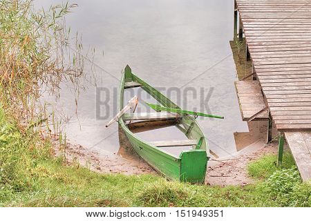 sinking abandoned boat on a lake shore, wooden jetty
