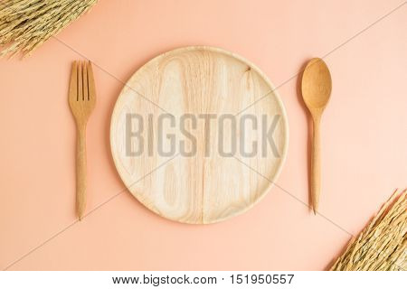 Top view of empty wooden plate fork spoon with dried paddy rice on light orange background