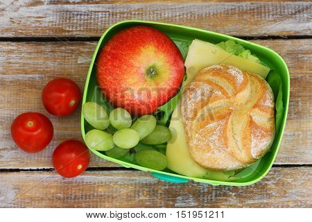 School lunch box with cheese sandwich, red apple, grapes and cherry tomatoes