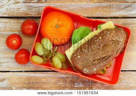 Healthy school lunch box with brown bread cheese sandwich, mandarine, grapes and cherry tomatoes